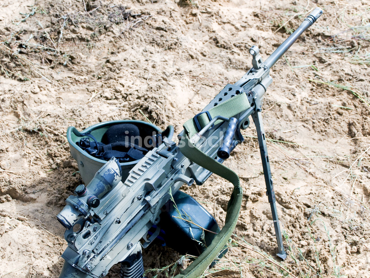 Soldier helmet and assault rifle on the sand