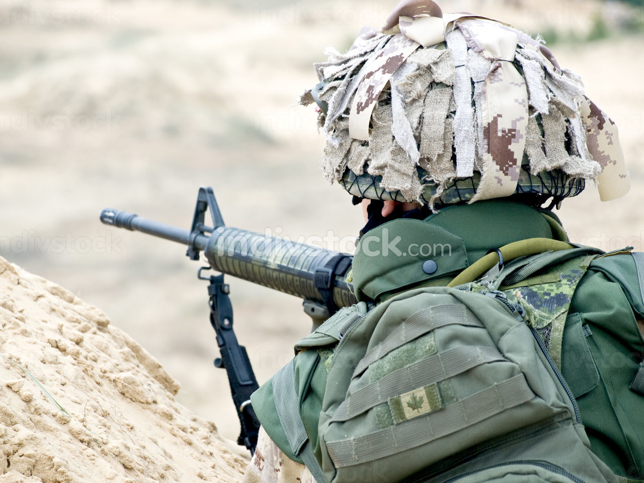 soldier in desert uniform aiming his rifle
