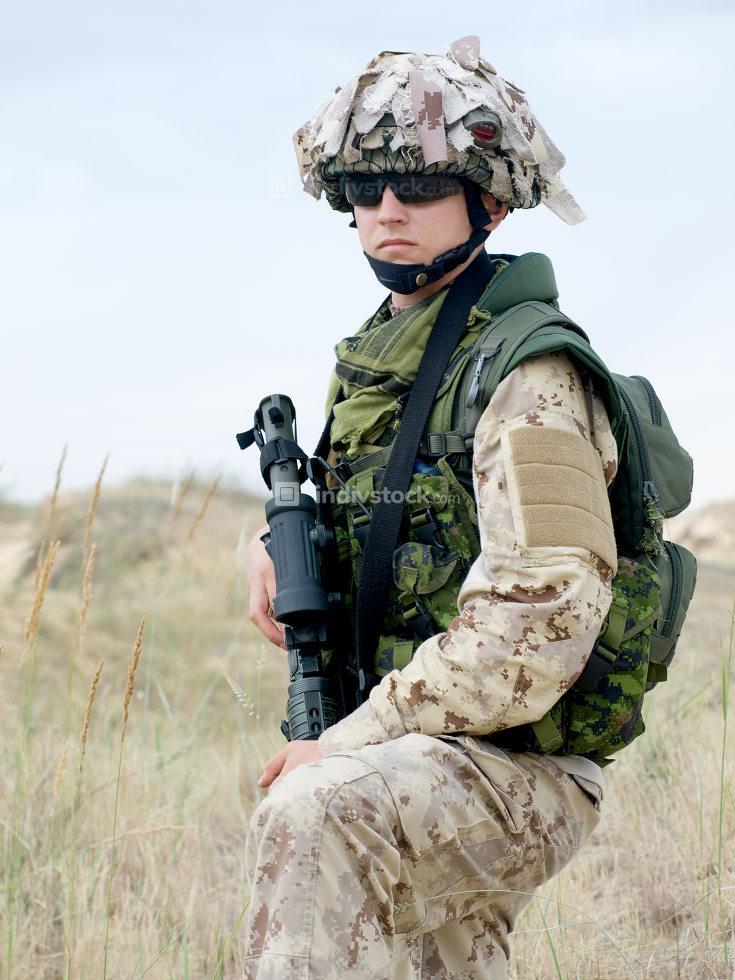 soldier in desert uniform holding his rifle
