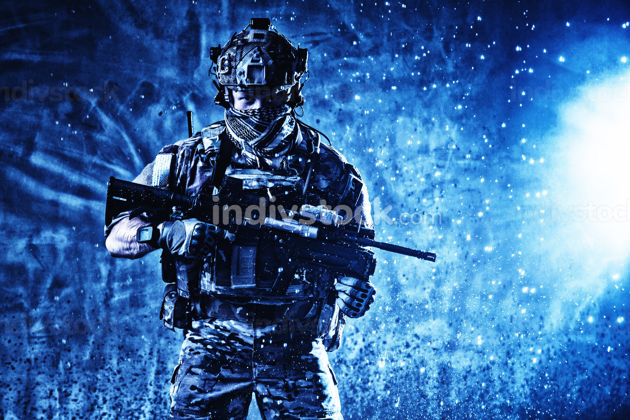 Soldier in tactical ammunition, wearing camo uniform, battle helmet, radio headset, hiding face behind scarf, standing with assault rifle in sparkles splash from explosion beside, looking in camera