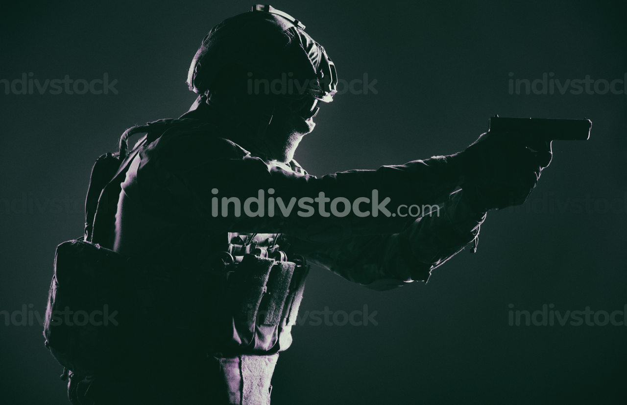 Soldier of army elite forces, special security service fighter with hidden behind mask and glasses face, in helmet and load carriage system, aiming with service pistol low key, side view, studio shoot