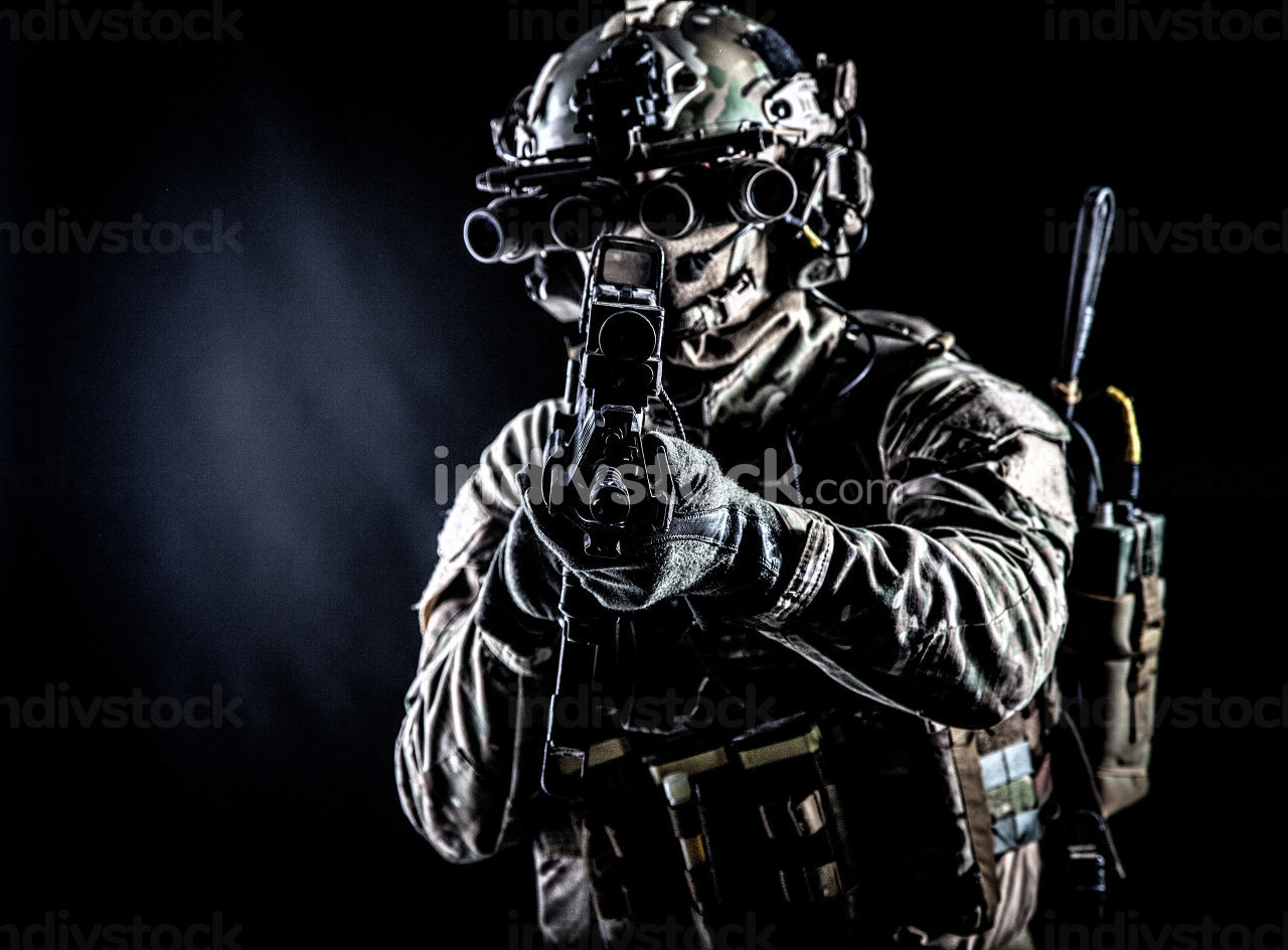 Soldier of special forces in camo combat uniform, load carrier, helmet, equipped night sight goggles, tactical radio headset, aiming assault rifle with collimator sight in camera, low key studio shoot