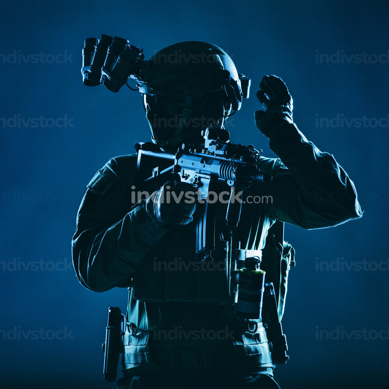 Special operations soldier, SWAT team fighter in mask and glasses, equipped night vision device, armed short barrel service rifle, looking back and showing freeze hand signal, low key studio shoot