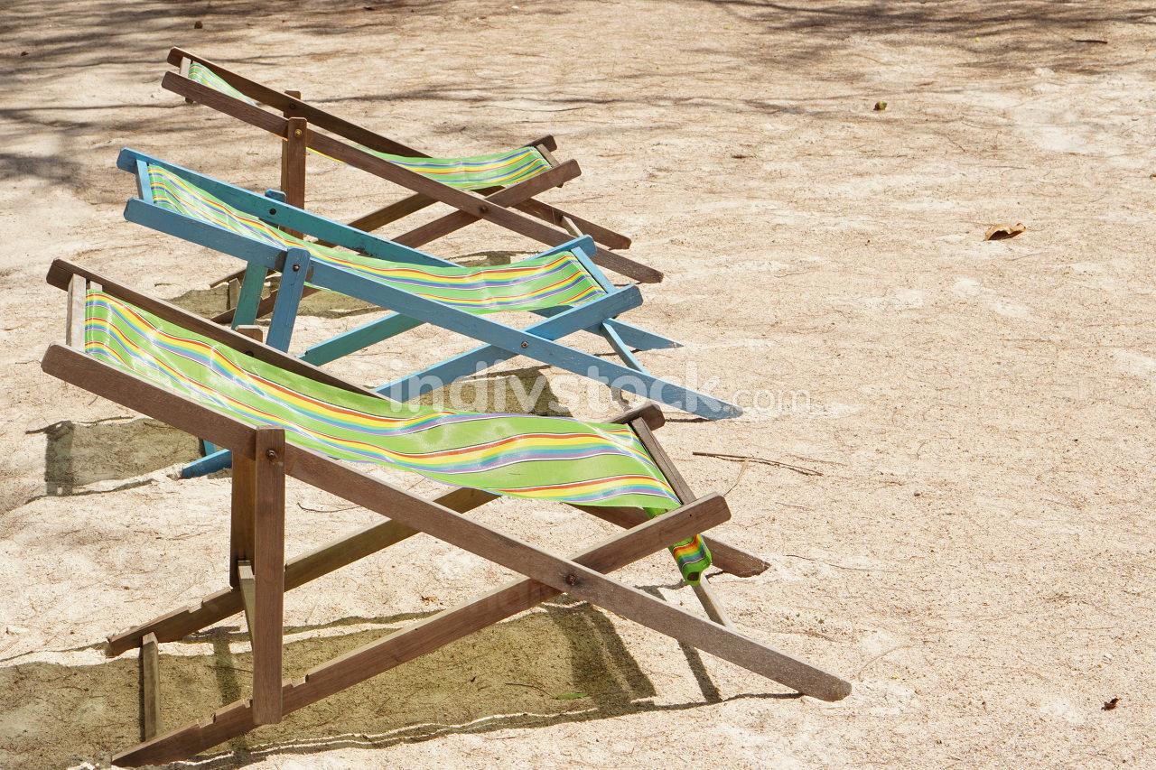sun loungers or deck chairs on a sandy beach