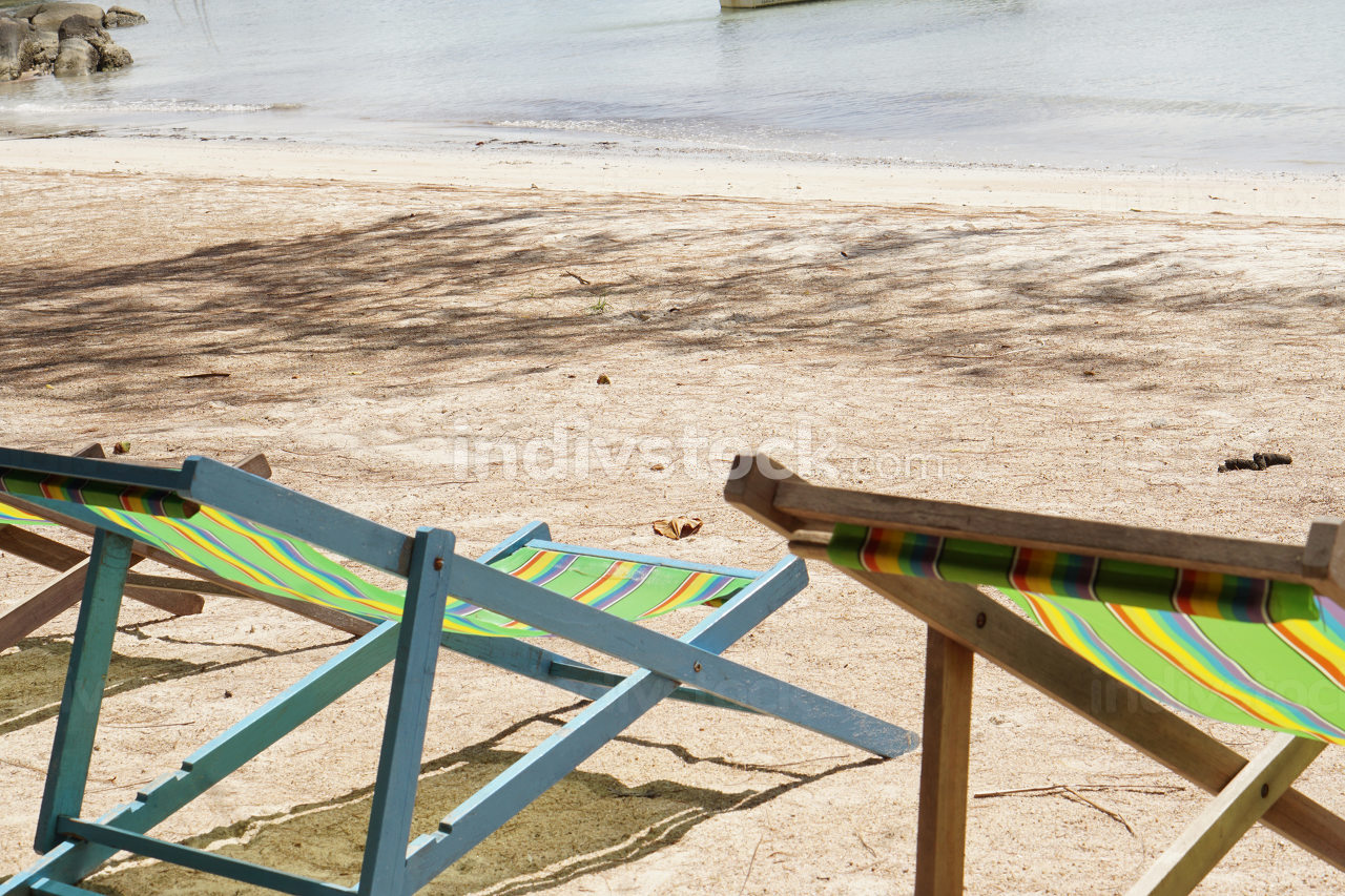 sun loungers or deck chairs on a sandy beach at the ocean in Koh Tao Thailand