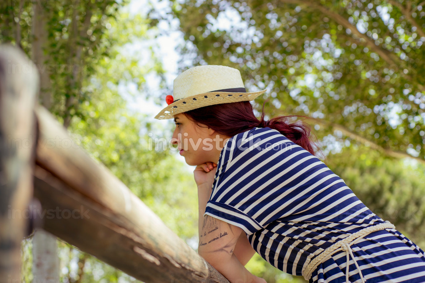 sunny spring scene, red haired girl with straw hat enjoying the