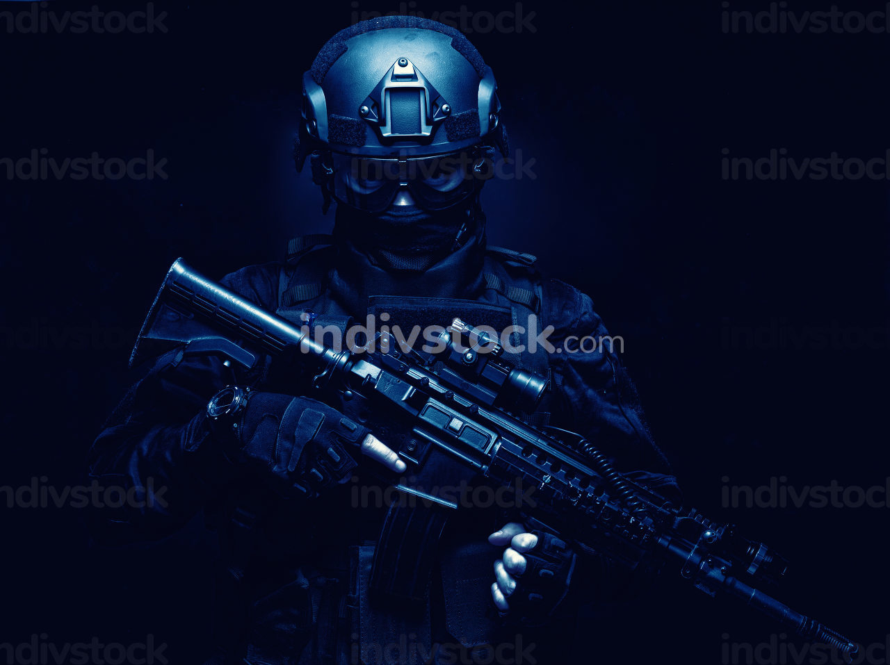 SWAT fighter, police tactical group member, quick reaction team shooter in black uniform, body armor, ballistic goggles and battle helmet, armed assault rifle with optical sight, standing in darkness