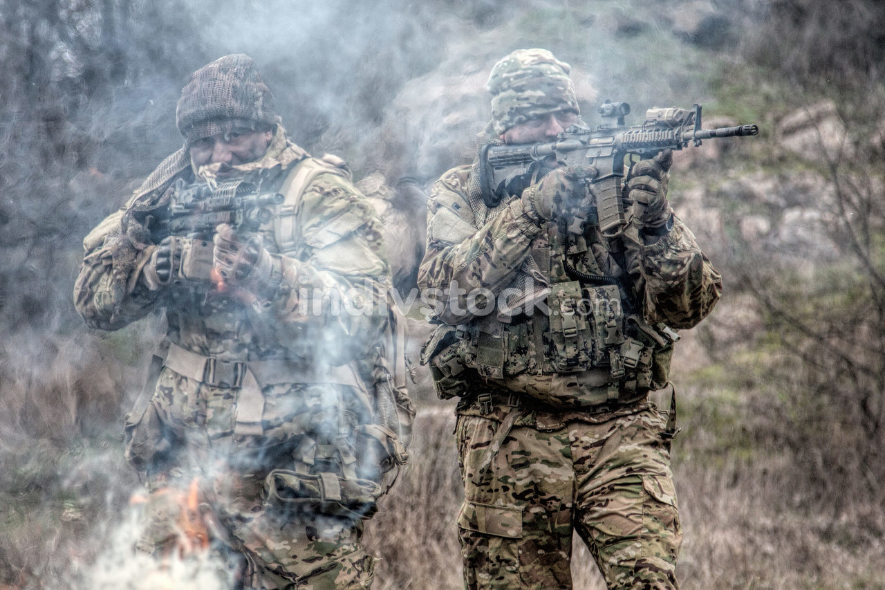 Two soldiers in camouflage uniform, wearing military ammunition, aiming service rifles, covering each other, shooting in competitors, attacking enemies trough smoke screen