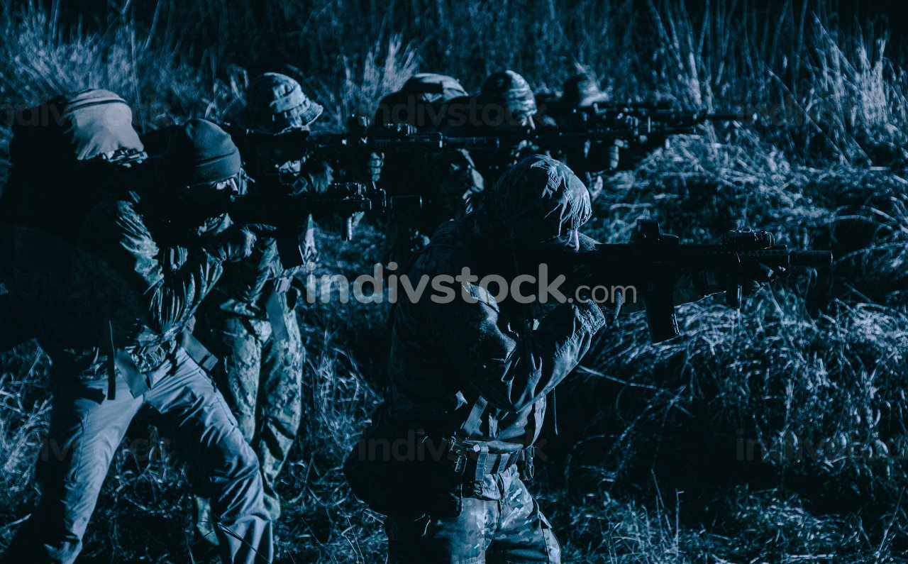 Two soldiers, special forces fighters, border guards team, counter-terrorism tactical group shooters aiming rifles, stopping offenders, attacking enemies during night patrolling, at sabotage mission