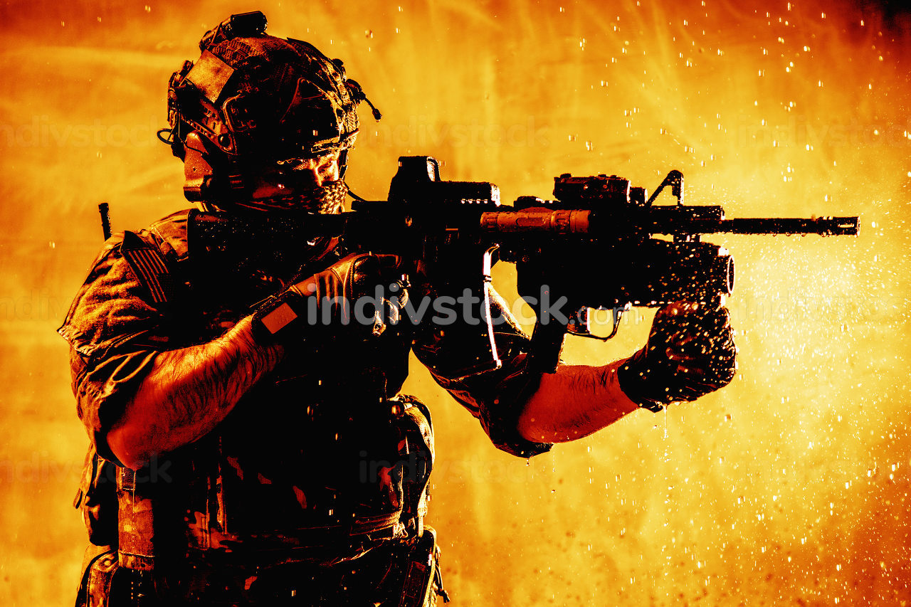 US army special forces shooter, modern combatant in battle helmet with radio headset, hiding face, aiming service rifle, fighting with enemies, shooting targets on fiery background with water droplets