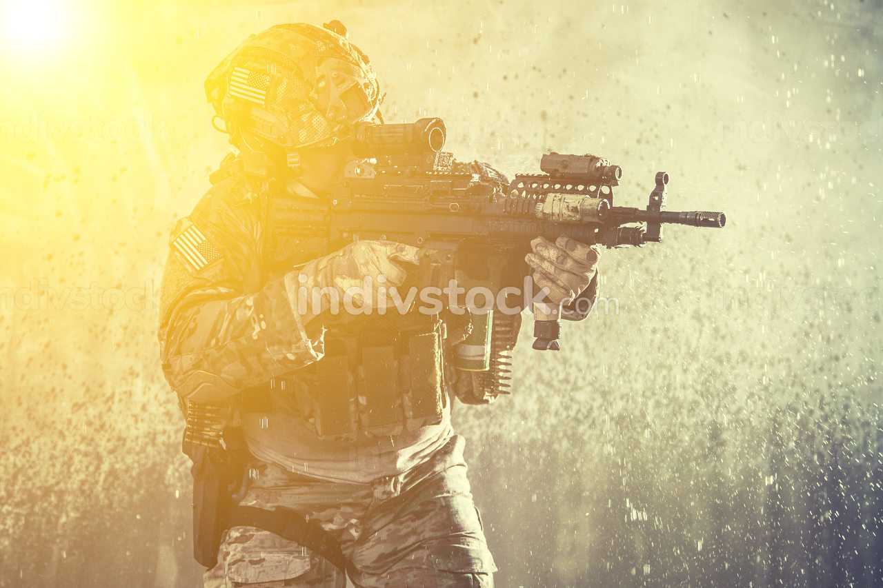 US marine riders machine gunner loaded with ammunition, in battle uniform and helmet, armed light machine gun, pistol and grenade, landing on seacoast, standing on background with sand, water splashes