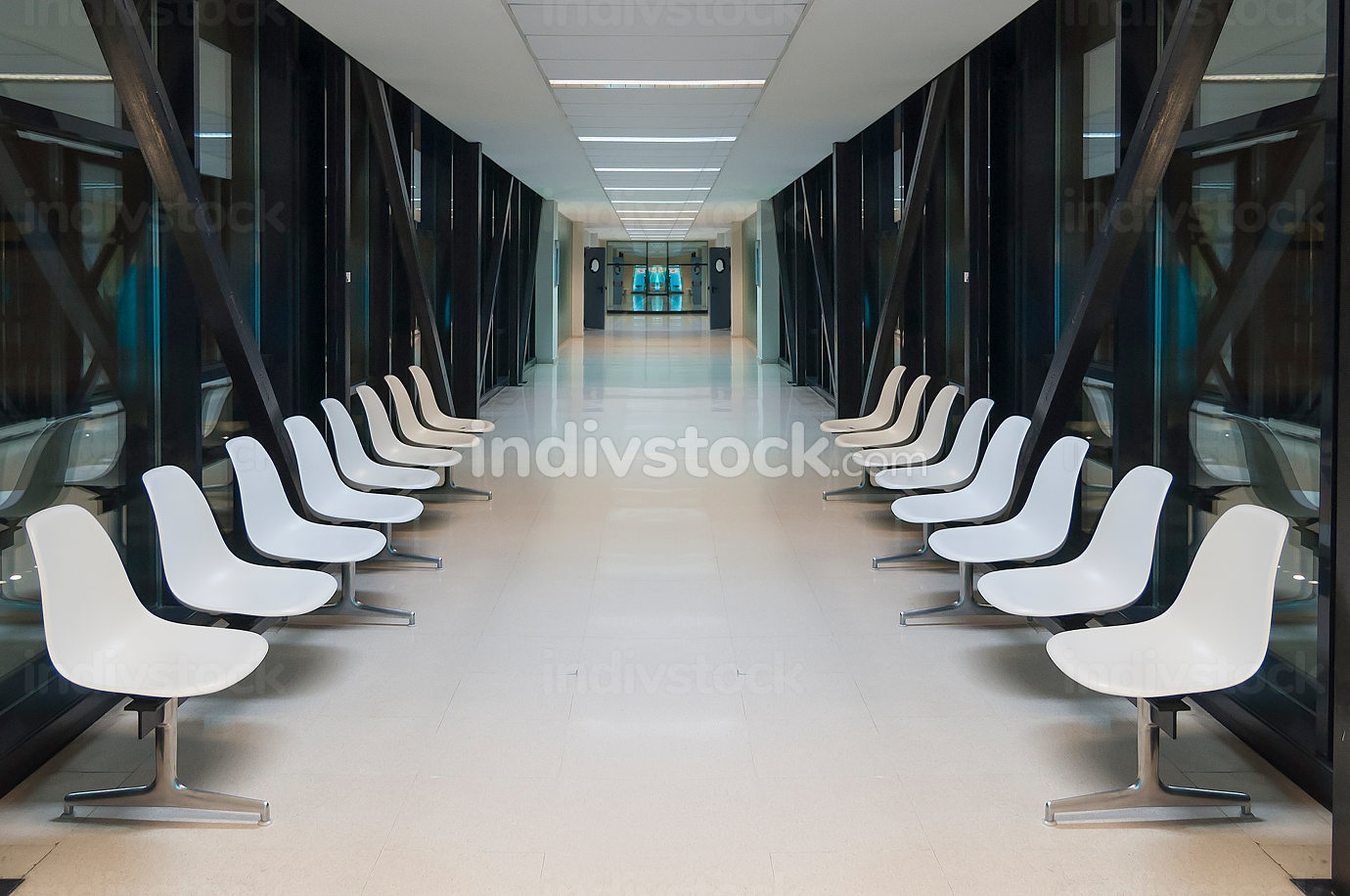 White hospital lobby with a door and white chairs for patients w