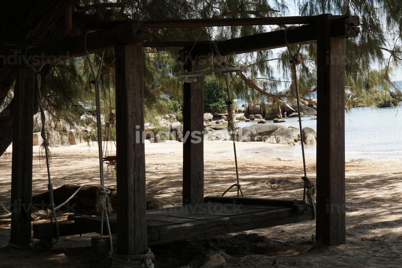 wooden swing at a sandy beach near the ocean in Koh Tao Thailand