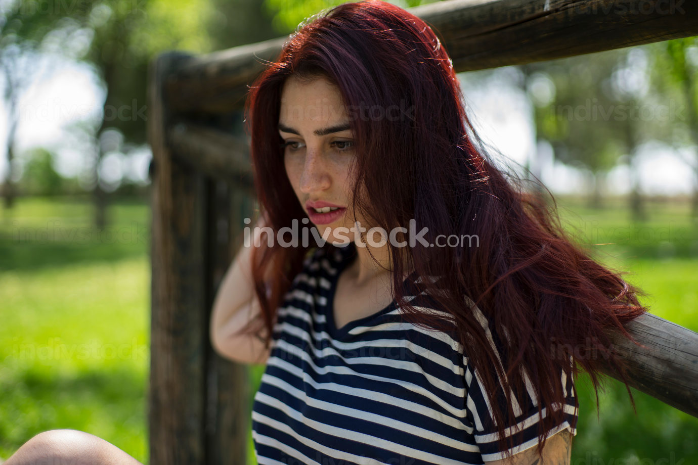 Young, sexy girl with long red hair in a park in summer