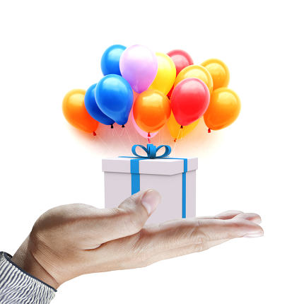 Hands holding gift in package with blue ribbon and colorful ball