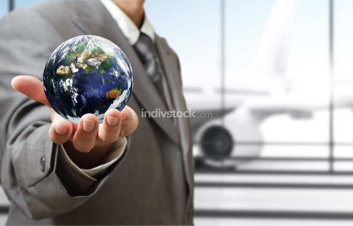 business man holds globe in the airport